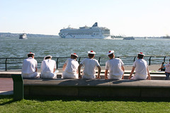 uniformed sailors sitting and looking at a far-off boat