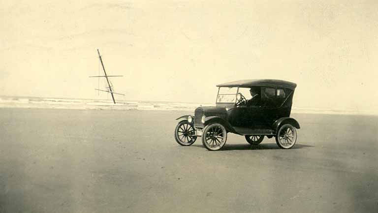 Automobile on a Pacific beach with shipwreck in background