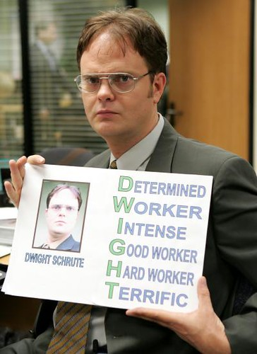 Dwight Schrute holding a sign displaying all his positive traits.
