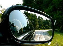 glasses(0.0), wheel(0.0), fisheye lens(0.0), windshield(0.0), sunglasses(0.0), driving(1.0), automobile(1.0), automotive exterior(1.0), automotive mirror(1.0), window(1.0), vehicle(1.0), automotive design(1.0), rear-view mirror(1.0), light(1.0), glass(1.0), green(1.0),