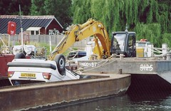 asphalt(0.0), vehicle(1.0), dredging(1.0), construction equipment(1.0), boat(1.0), waterway(1.0),