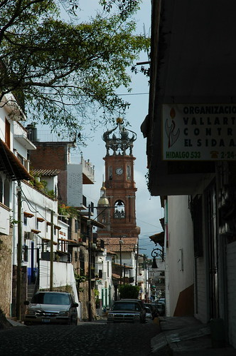 Cathedral of Our Lady of Guadalupe, Calvario, looking down an alleyway, to the east, bell tower, clock, crown of angels, trees, houses, Puerto Vallarta, Jalisco, Mexico by Wonderlane