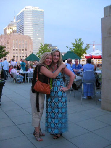 Carrie and Lori enjoy the rooftop gathering, with the Oklahoma City skyline in the background.
