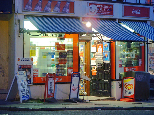 The front of a newsagent shop at night time