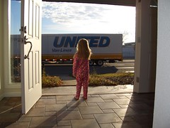 young girl in footie pajamas looks out the front door at a huge moving truck