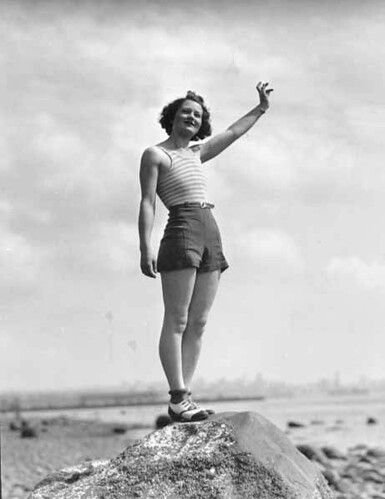 Woman in a swimsuit waving while standing on a large rock on a beach, probably Washington State