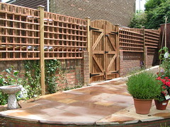 outdoor structure(0.0), handrail(0.0), deck(0.0), patio(0.0), walkway(0.0), courtyard(1.0), backyard(1.0), home fencing(1.0), fence(1.0), garden(1.0), wall(1.0), wood(1.0), landscaping(1.0), brickwork(1.0),