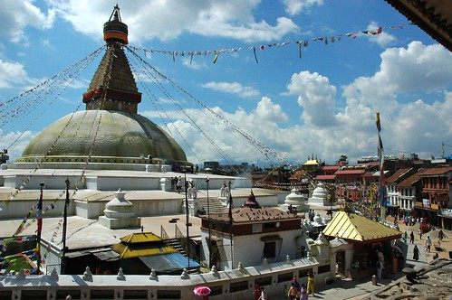 Sur offering on the steps of the Boudha Stupa, as seen from the northeast view of the shrine and candle offering rooms, on a sunny day with puffy clouds, Boudha, Kathmandu, Nepal by Wonderlane