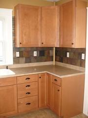 furniture(0.0), bathroom cabinet(0.0), bathroom(0.0), floor(1.0), kitchen(1.0), countertop(1.0), wood(1.0), room(1.0), cupboard(1.0), wood stain(1.0), hardwood(1.0), cabinetry(1.0), sink(1.0),