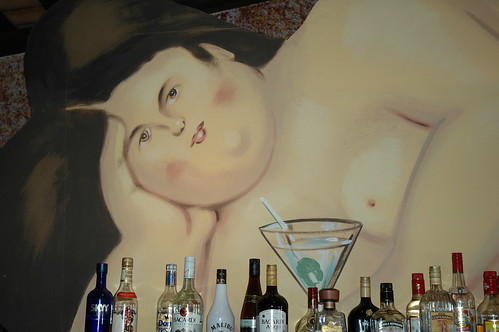 Portrait of a nude over the bar, that faraway look in her brown eyes, bottles of alcohol, cocktail, Puerto Vallarta, Mexico by Wonderlane