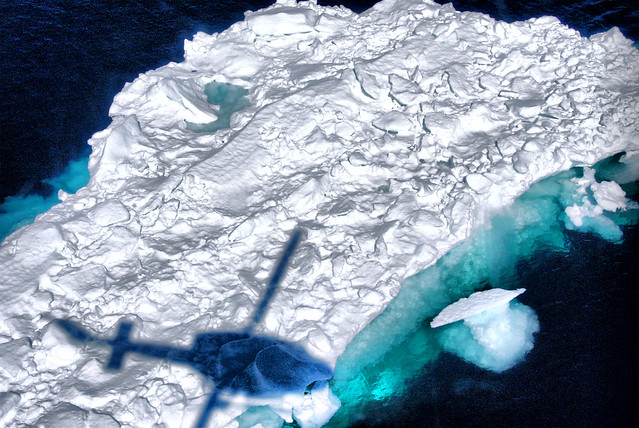 Helicóptero sobrevolando un iceberg en Tasiilaq, Groenlandia.