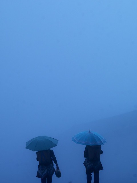 Two women with umbrellas in the fog and rain in Yuanyang, Yunnan, China