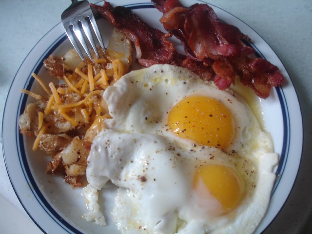 Photo:Two eggs sunny side up, bacon, and home fries with cheddar cheese By:@joefoodie