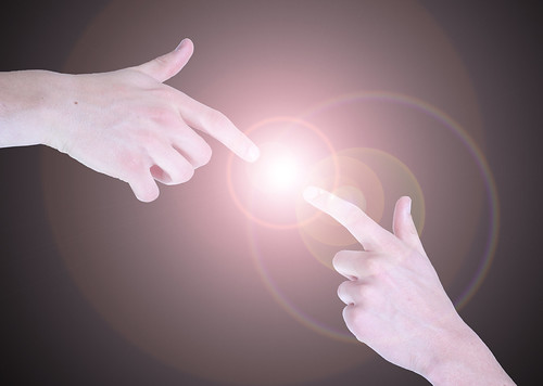 A  Photograph of Fingers Touching a Bright Light