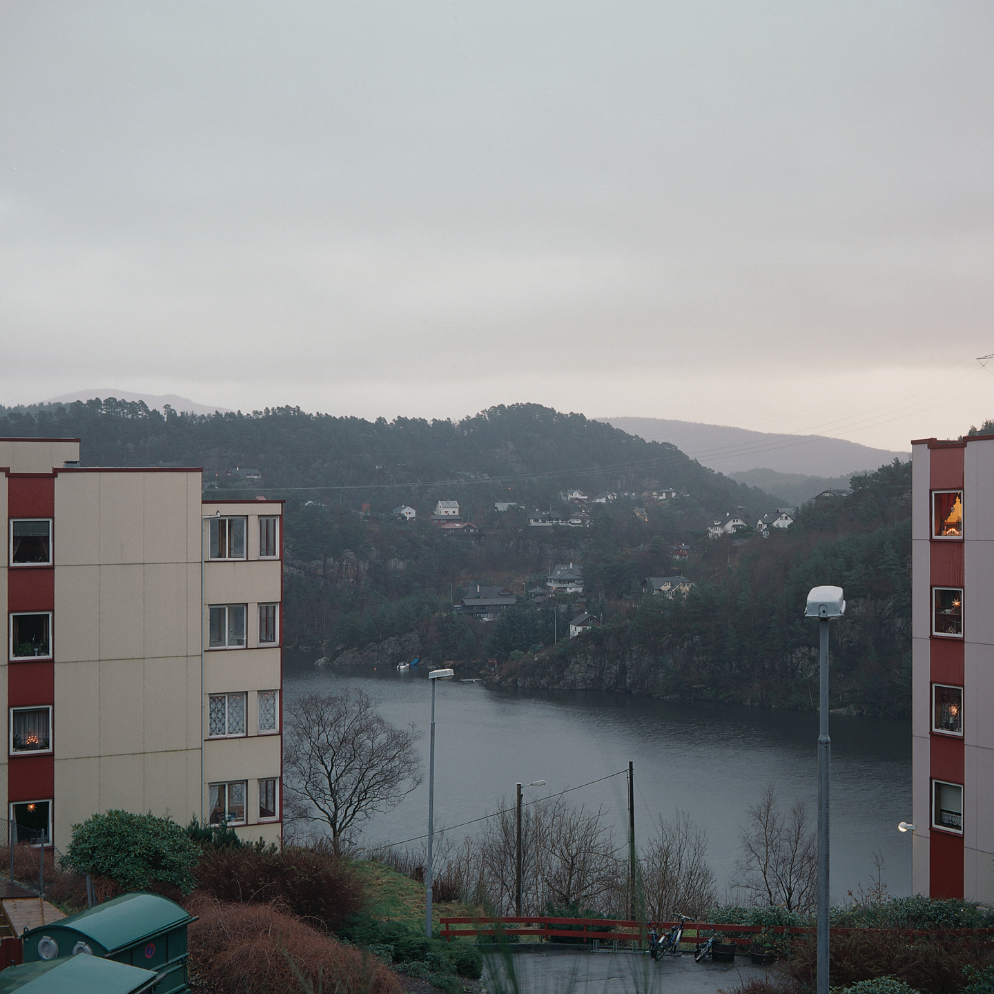 Parts of two apartment buildings, view of hills and water between them.