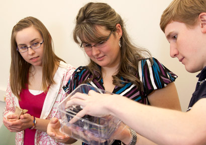 Newman University students looking at a computer part