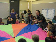 Story time with Mr. K leading children and parents in a movement activity in the Almaden Library Program Room