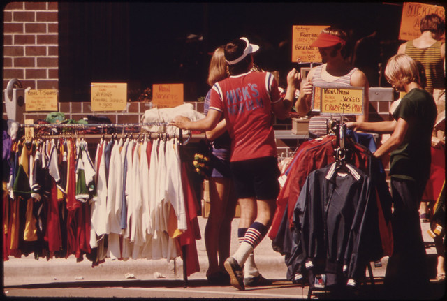 People Looking over Bargains Among Merchandise Placed in Minnesota Street and on Side-Walks by Merchants in New Ulm Minnesota, During Their Annual Crazy Days Sale...