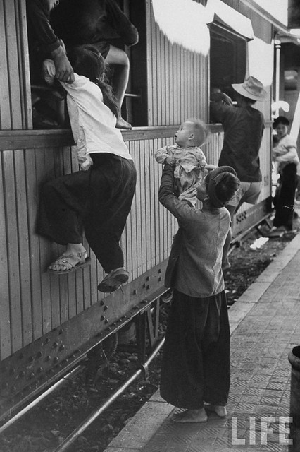 76a Hanoi residents carrying belongings and children climbing into train to flee south after Communist takeover 1954