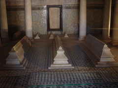 'The Saadian tombs in Marrakech date back from the time of the great sultan Ahmad I al-Mansur (1578-1603). The tombs were only recently discovered (in 1917) and were restored by the Beaux-arts service. The tombs have, because of the beauty of their decoration, been a major attraction for visitors of Marrakech.The mausoleum comprises the corpses of about sixty members of the Saadi Dynasty that originated in the valley of the Draa River. Among the tombs are those of Ahmad I al-Mansur and his family. The building is composed of three rooms. The most famous is the room with the twelve columns. This room contains the tomb of the son of the sultan's son Ahmed El Mansour. The stele is in finely worked cedar wood and stucco work. The graves are made of Italian Carrara marble.Outside the building is a garden and the graves of soldiers and servants.'en.wikipedia.org/wiki/Saadian_Tombs
