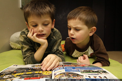 brothers poring over a lego catalog that arrived in today's mail