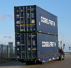 billboard(0.0), vehicle(1.0), transport(1.0), shipping container(1.0), cargo(1.0), advertising(1.0),