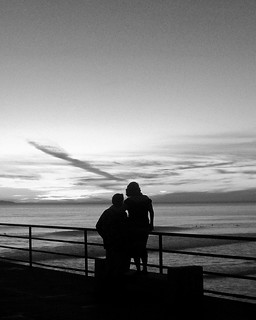 silhouetted couple watching sunset black and white