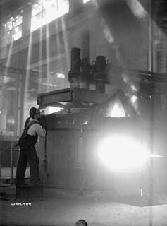 Workman operates furnace used to melt bomb-making materials at the Cherrier plant. / Un ouvrier fait fonctionner un four utilisé pour fondre les matériaux entrant dans la fabrication de bombes à l'usine Cherrier