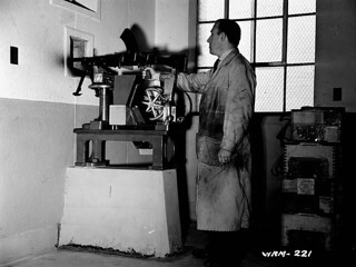 Tester fires off round from completed Bren gun in special test room. / Un technicien d'essai tire une balle de fusil-mitrailleur Bren dans une salle d'essai spéciale
