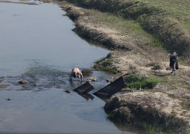 Man taking bath in a cold river - North Korea