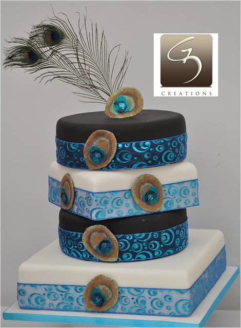 The top of the cake showcases real peacock feathers