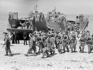 Canadian troops disembarking from a landing craft during a training exercise before the raid on Dieppe, August 1942 / Soldats canadiens descendant d'une barge de débarquement lors d'un exercice d'entraînement avant le raid sur Dieppe, août 1942
