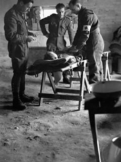 A wounded Canadian soldier is examined before being evacuated to a field surgical unit, Italy, January 1944 / Un soldat canadien blessé est examiné avant d'être transporté vers une unité chirurgicale de campagne, Italie, janvier 1944