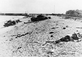 View looking east along the main beach at Dieppe, showing damaged Churchill tanks of the Calgary Regiment / Vue vers l'est de la plage principale de Dieppe montrant des chars d'assaut « Churchill » du Régiment de Calgary endommagés