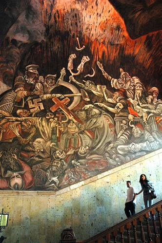 Scale of the large and overwhelming murals, a couple descending the staircase, The Clowns of War Arguing in Hell, depicting war mongers with their political agendas and logos, José Clemente Orozco Mural, Governor's Palace, Guadalajara, Jalisco, Mexico by Wonderlane