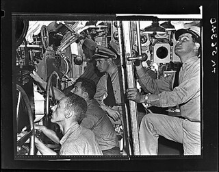 Lcdr. John R. Madison prepares to go up ladder from control room of USS Muskallunge (SS 262) at submarine base New London, Connecticut. Lt. William B. Robb is at his station., 08/1943