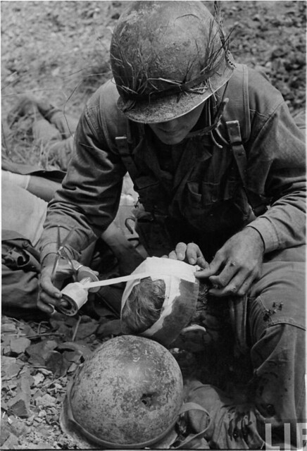 Beside his bullet-riddled helmet, a Marine receives treatment for a head wound on Okinawa, by W. Eugene Smith 1945