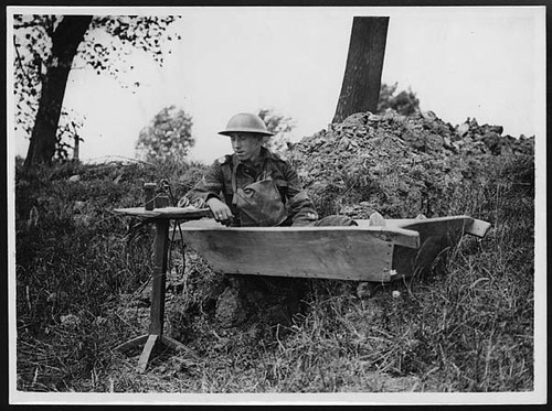 Signaller with his instruments makes himself a comfortable seat in an old bath tub