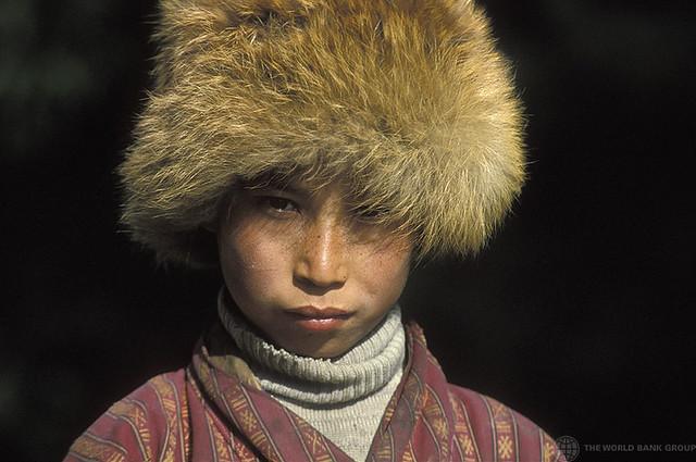 Portrait of young boy wearing fur hat. Bhutan. Portrait. Bhutan.