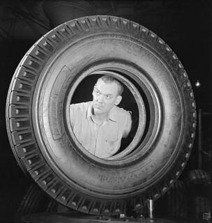 Workman John Seliger makes the final inspection of a new synthetic rubber tire at the Dominion Rubber plant. / À l'usine Dominion Rubber, l'ouvrier John Seliger effectue une dernière vérification d'un nouveau pneu de caoutchouc synthétique