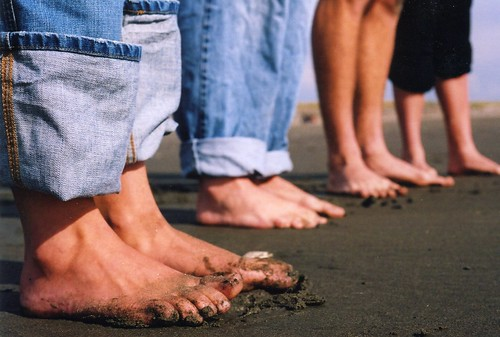 family's bare feet on beach