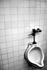 floor(0.0), room(0.0), circle(0.0), bidet(0.0), flooring(0.0), sink(0.0), toilet(1.0), white(1.0), monochrome photography(1.0), urinal(1.0), plumbing fixture(1.0), tap(1.0), tile(1.0), monochrome(1.0), bathroom(1.0), black-and-white(1.0), black(1.0),