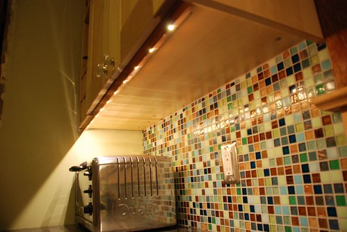 undercabinet lighting with toaster oven and mosaic backsplash
