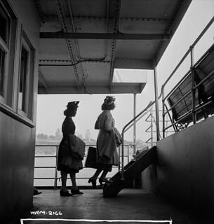 Two female Dominion Arsenals Ltd. munitions plant workers cross the river to Québec, Canada by ferry. / Deux ouvrières des munitions de l'usine de la Dominion Arsenals Ltd. empruntent le traversier pour se rendre à Québec, Canada