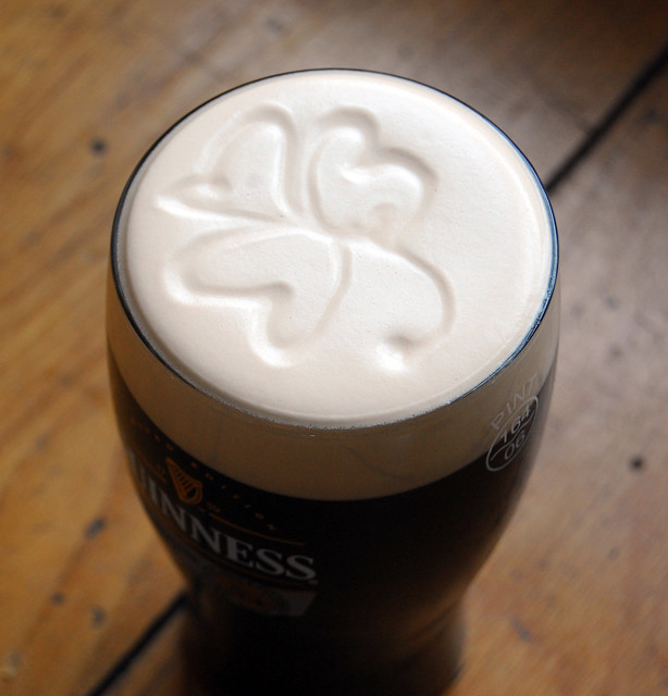 logo in the foam irish clover in a pint of guiness at