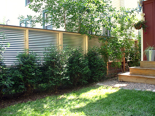 fence with reclaimed lumber and corrugated steel