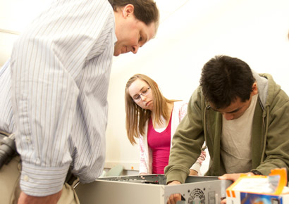Newman University students fixing a computer in class