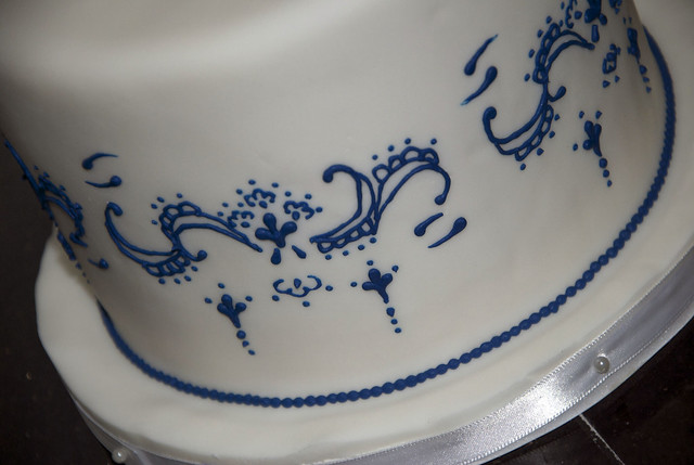 A 6 round white fondant covered wedding cake with royal blue piping for the