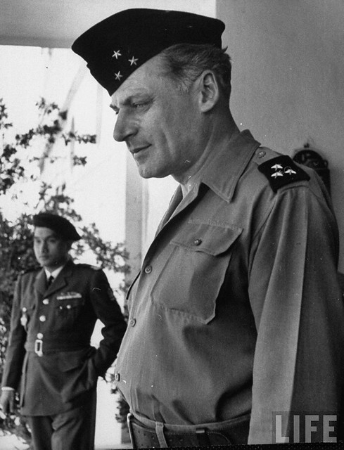 Hanoi, March 1954 - Gen. Rene Cogny, French Army commander, face very serious and rather sad, as he futifully walks behind the absentee playboy ruler of Annam, Bao Dai