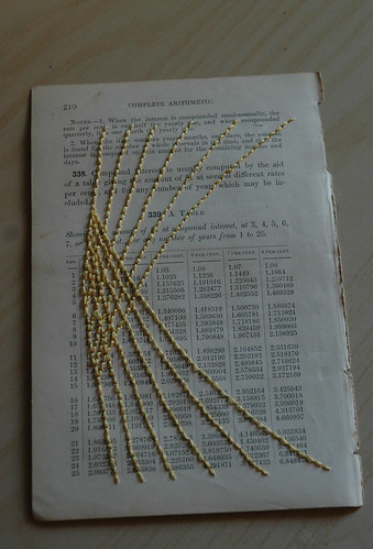 A page of a book on arithmetic, stitched with yellow thread.